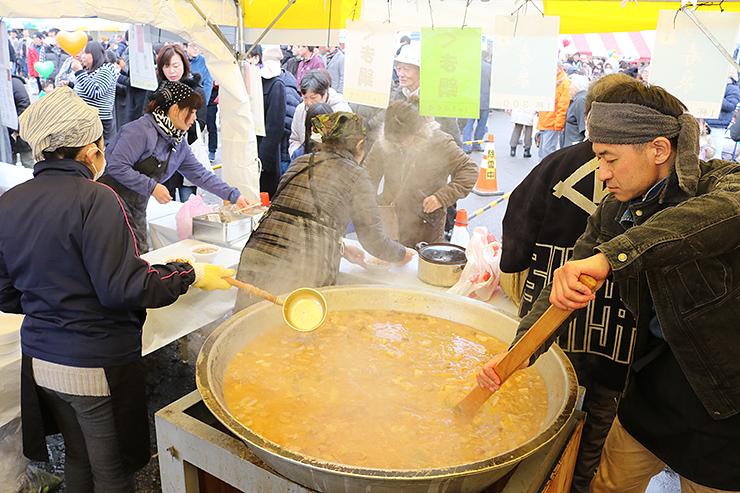 大鍋で作られたくま鍋などのブースが並んだ会場=上市町役場駐車場