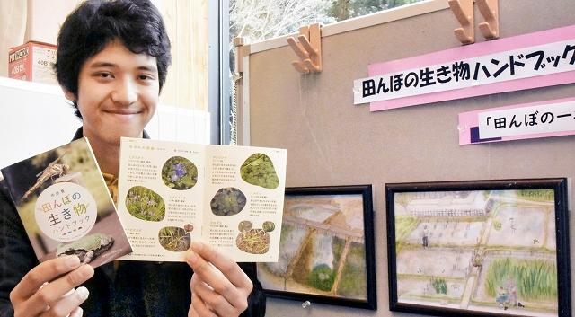 ハンドブックを片手に湿地を散策してほしいと話す藤野勇馬さん=2月8日、福井県敦賀市の中池見湿地ビジターセンター