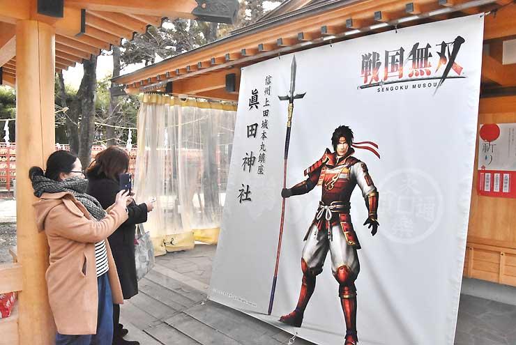 「戦国無双」シリーズの真田幸村が描かれた幕を撮影する観光客
