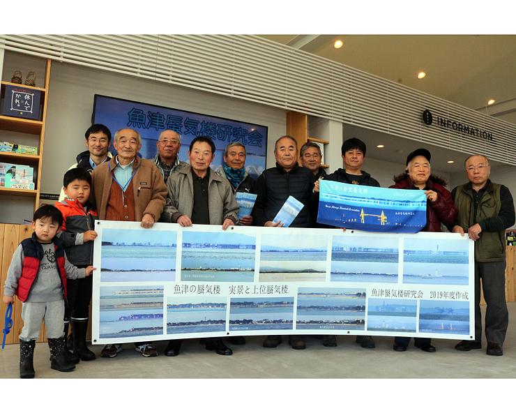 7年ぶりに更新した横断幕を紹介する魚津蜃気楼研究会員ら=海の駅・蜃気楼