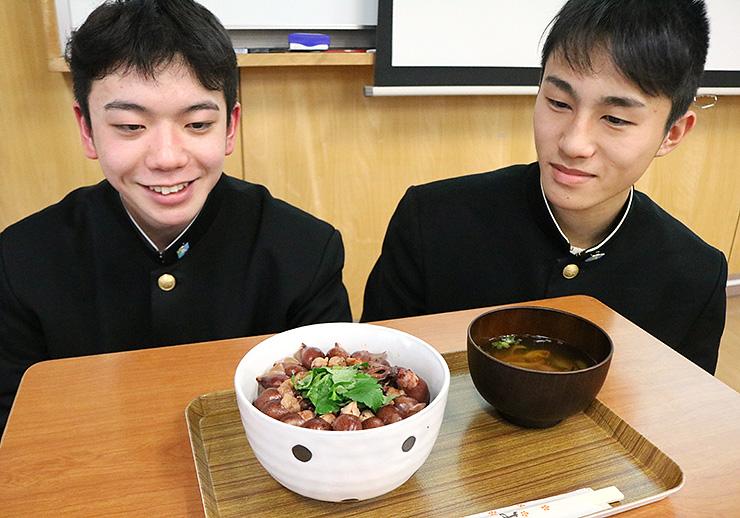 ホタルイカがぎっしり並んだ丼。長岡さん(右)や十松さんらのグループが考案した