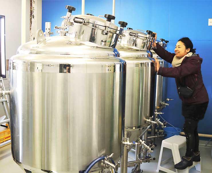 新しく導入した醸造用タンクの動作を確認する冨成さん