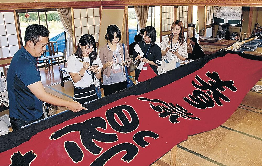 地元住民から枠旗の説明を受ける学生=昨年9月、七尾市中島町中島