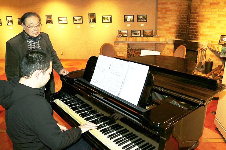 鈴木さんが作った「北陸秋景」の演奏に耳を傾ける河田会長=宇奈月国際会館セレネ