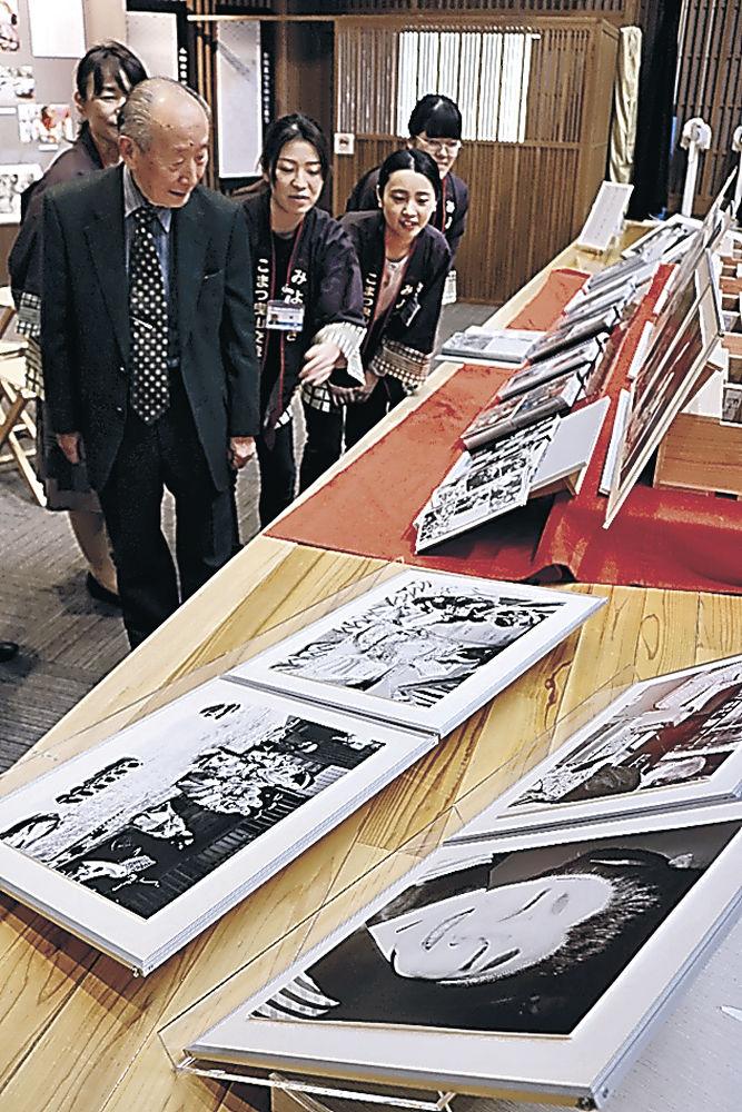 寄贈した写真を説明する宮腰さん(左)=小松市のこまつ曳山交流館みよっさ