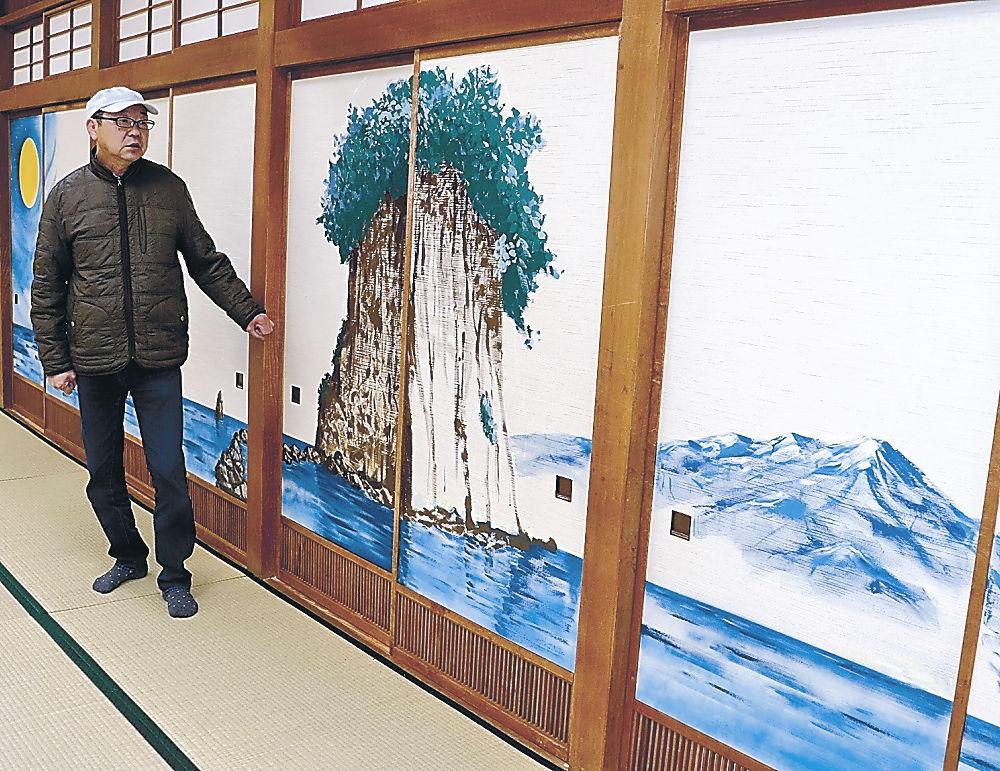 見附島を描いたふすまの前に立つ濵形さん=珠洲市宝立町鵜飼の国民宿舎