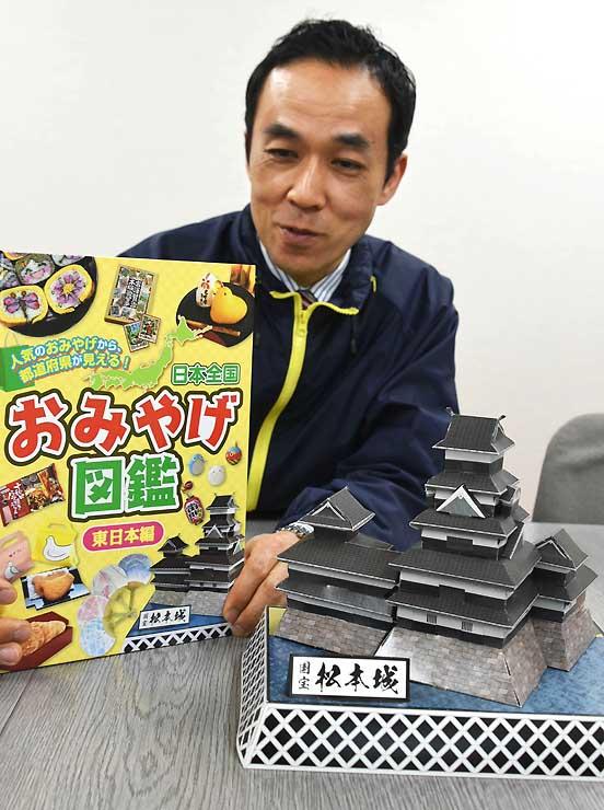 「ペーパークラフト国宝松本城」の完成品(右)と商品を表紙に掲載した「日本全国おみやげ図鑑」