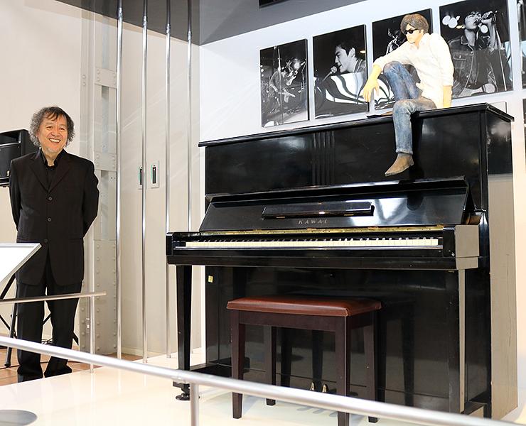 寄贈されたピアノと並ぶ須藤さん=富山市民芸術創造センター