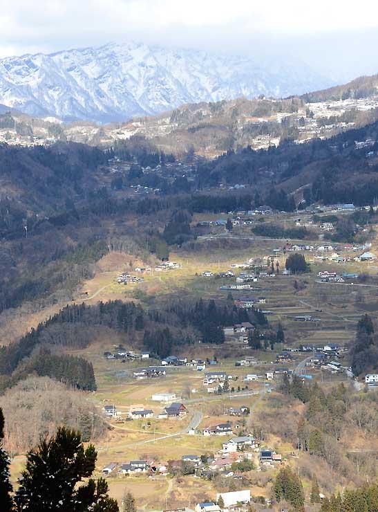 峰街道沿いから見た戸隠連峰(奥)や集落の眺め=2017年12月