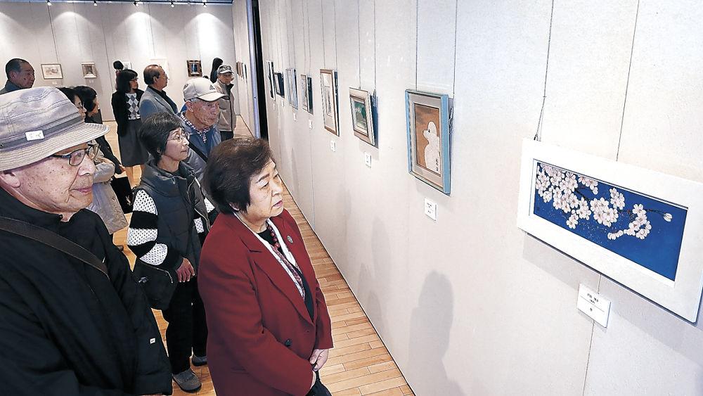 会場に並ぶ絵画を鑑賞する来場者=北國新聞交流ホール