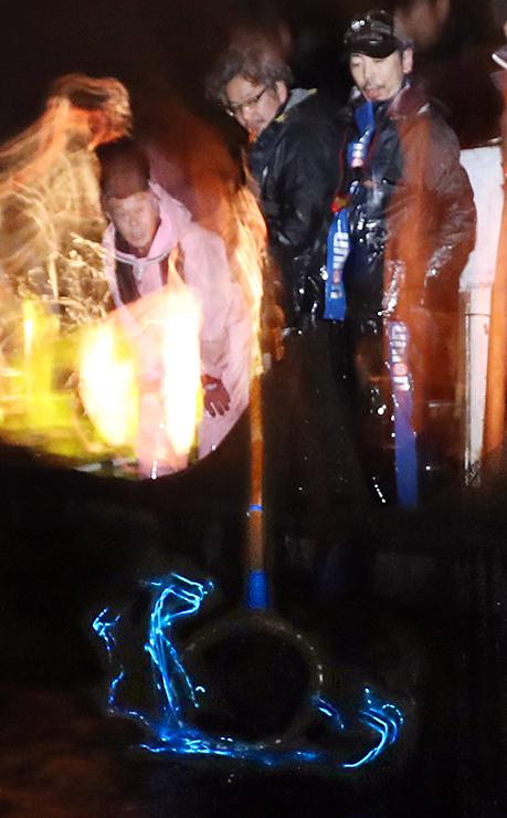 網に掛かり青白く光るホタルイカ=1日午前5時ごろ、滑川市沖