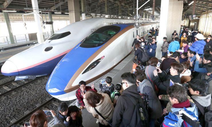 上越新幹線に導入される「E7系」(手前)と写真を撮る家族連れ=2日、JR新潟駅