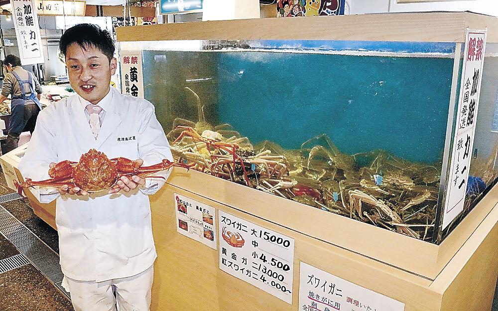 低温水槽で管理した県産カニを販売する高橋さん=七尾市の能登食祭市場