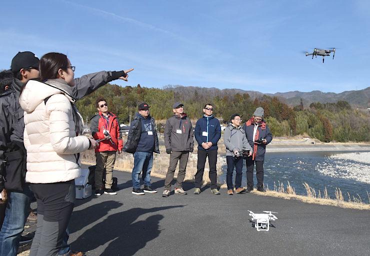 ドローンを飛ばして、天竜川(右)を空撮して楽しむ参加者たち=中川村