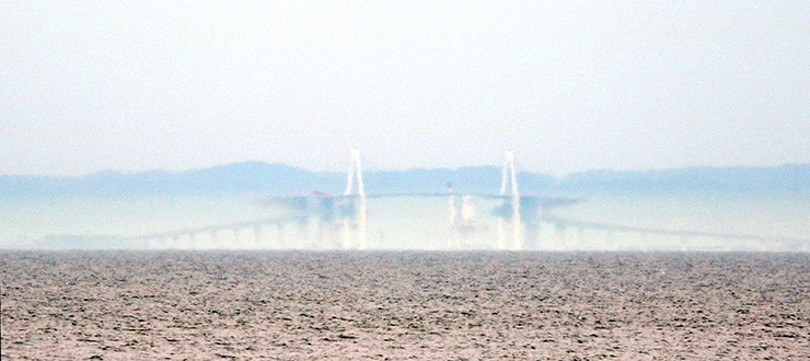 新湊大橋中央が上下反転し、両端が「Z」の形に見えた春型蜃気楼=10日午後1時半ごろ