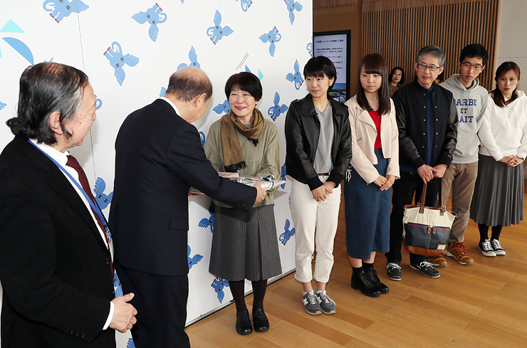石井知事から200万人目の記念品を受け取る澤田さん(左から3人目)。右側は前後の来館者=富山県美術館