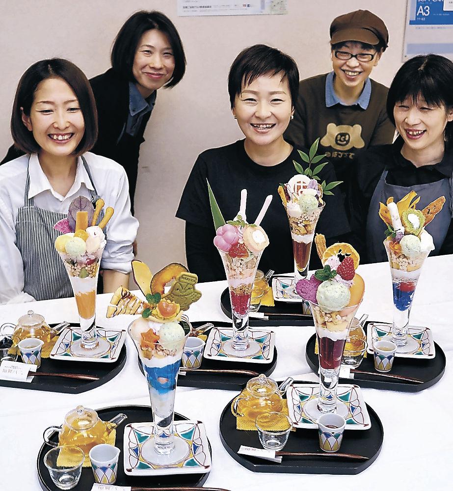 加賀パフェの新作と開発した各店舗の関係者=加賀市民会館