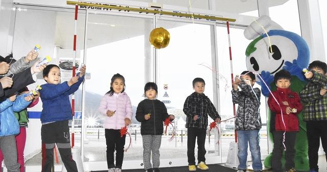 クラッカーを鳴らすなどして観光船の今季運航開始を祝う園児たち=3月11日、福井県おおい町成海の「うみんぴあ大飯」