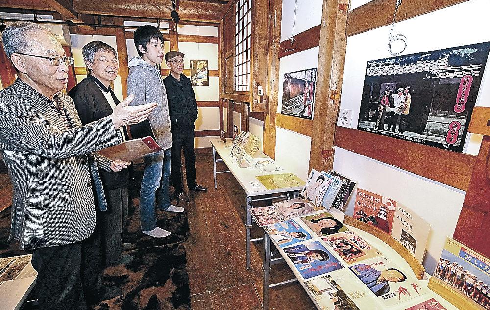 展示資料の由来を解説する伊藤さん(左)=片町2丁目の金沢学生のまち市民交流館