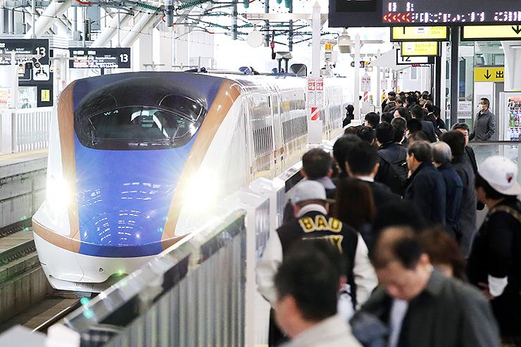 大勢の乗客が待つホームに入る北陸新幹線「かがやき508号」=14日午前10時5分ごろ、JR富山駅
