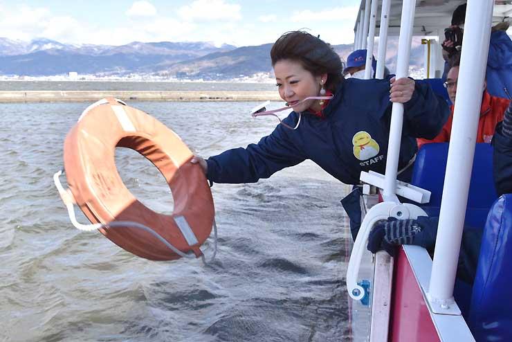 救助訓練で、湖面に落ちた人を想定して浮輪を投げる水陸両用バスのガイド