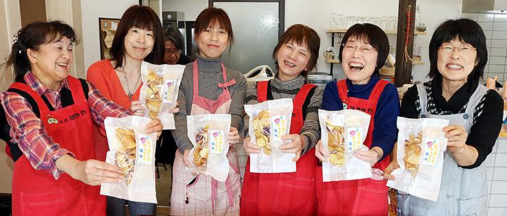 商品化したサツマイモのチップスを手に笑顔があふれるメンバー