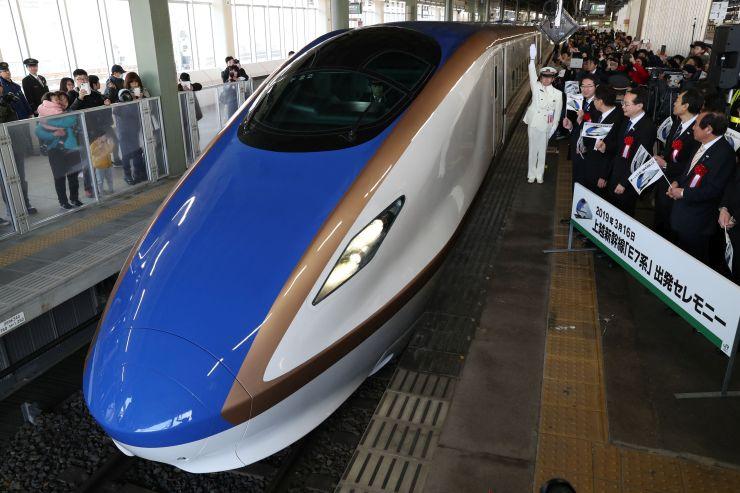 上越新幹線に導入され、新潟駅を出発するE7系の新幹線車両=16日、新潟市中央区