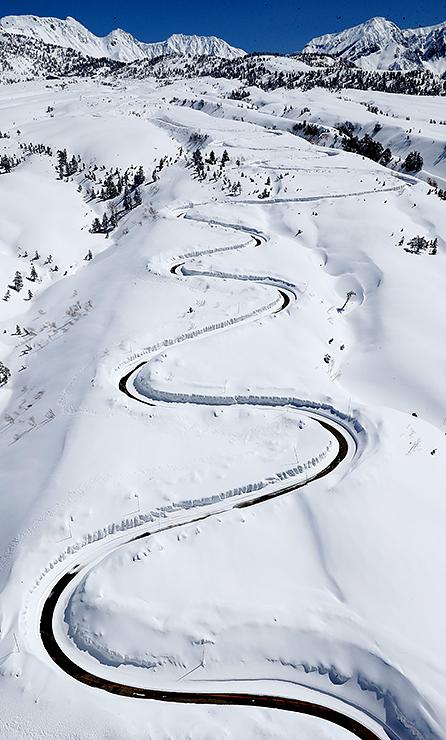 雪原に浮かび上がる除雪された高原バス道路の曲線=18日午前11時40分ごろ、立山・七曲付近、本社チャーターヘリから