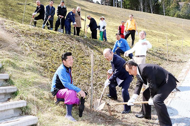 モミジの苗木を植樹する松本会長(手前右から2人目)ら。地元経営者らがスコップやくわを手に作業した