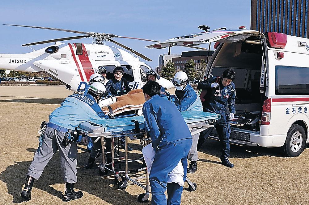 訓練でドクターヘリに引き継ぐ手順を確かめる参加者=金沢市の鞍月セントラルパーク