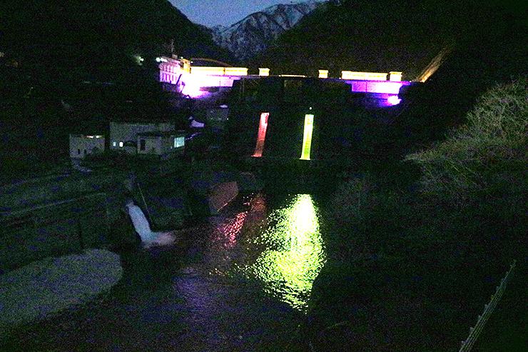 左からピンク、赤、黄、紫色にライトアップされた宇奈月ダム=ホテル黒部から撮影