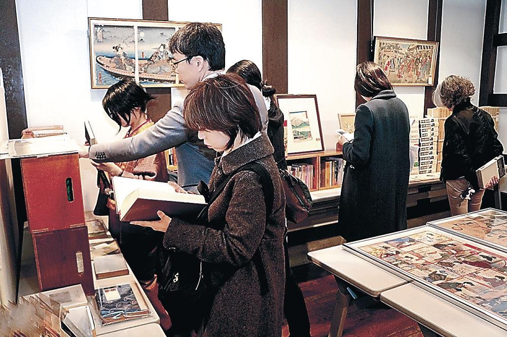金沢三文豪の関連古書を品定めする来場者=泉鏡花記念館