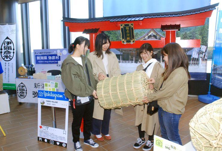 「伊彌彦米」の米俵を手に笑顔を見せる観光客=20日、東京都墨田区
