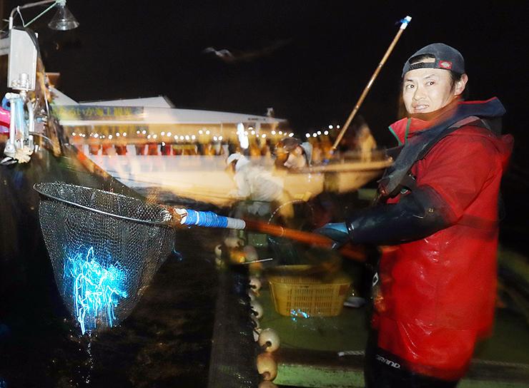 観光船試乗会で、たもの中で光るホタルイカ=19日、滑川沖