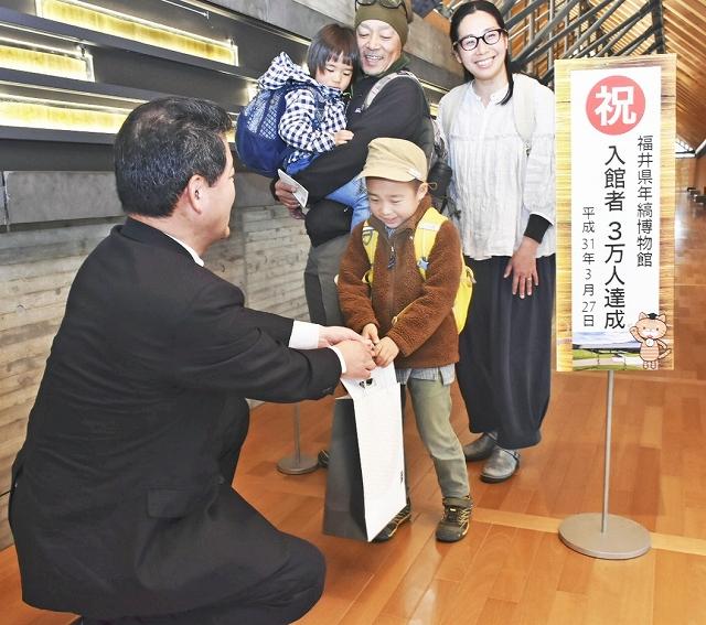 3万人目の入館者となった長野県の家族=3月27日、福井県若狭町鳥浜の県年縞博物館