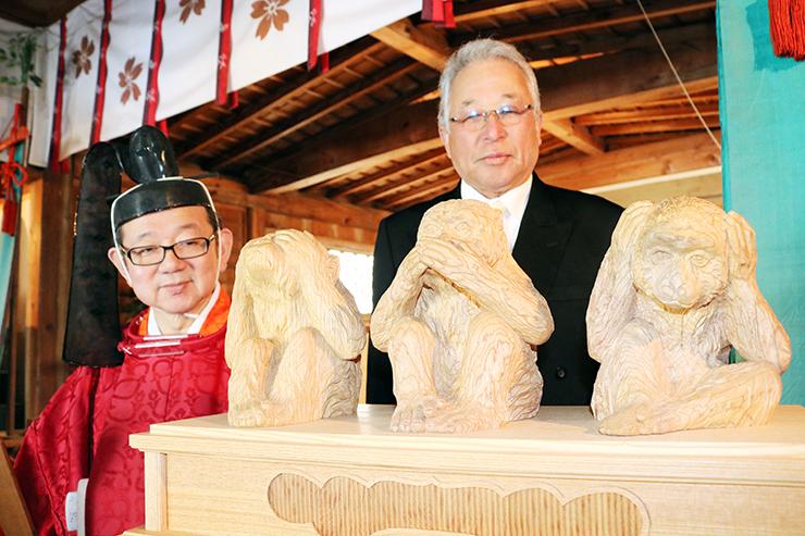 大伴宮司(左)が奉納した三猿の木像を見る花木代表