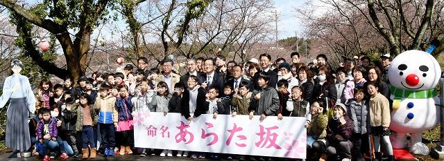「あらた坂」記念碑の建立を祝って記念撮影に収まる地元住民ら=3月31日、福井県あわら市自由ケ丘2丁目