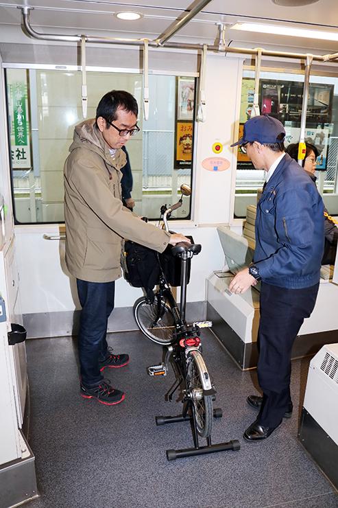 サイクルトラムに自転車を持ち込む利用客(左)=万葉線高岡駅
