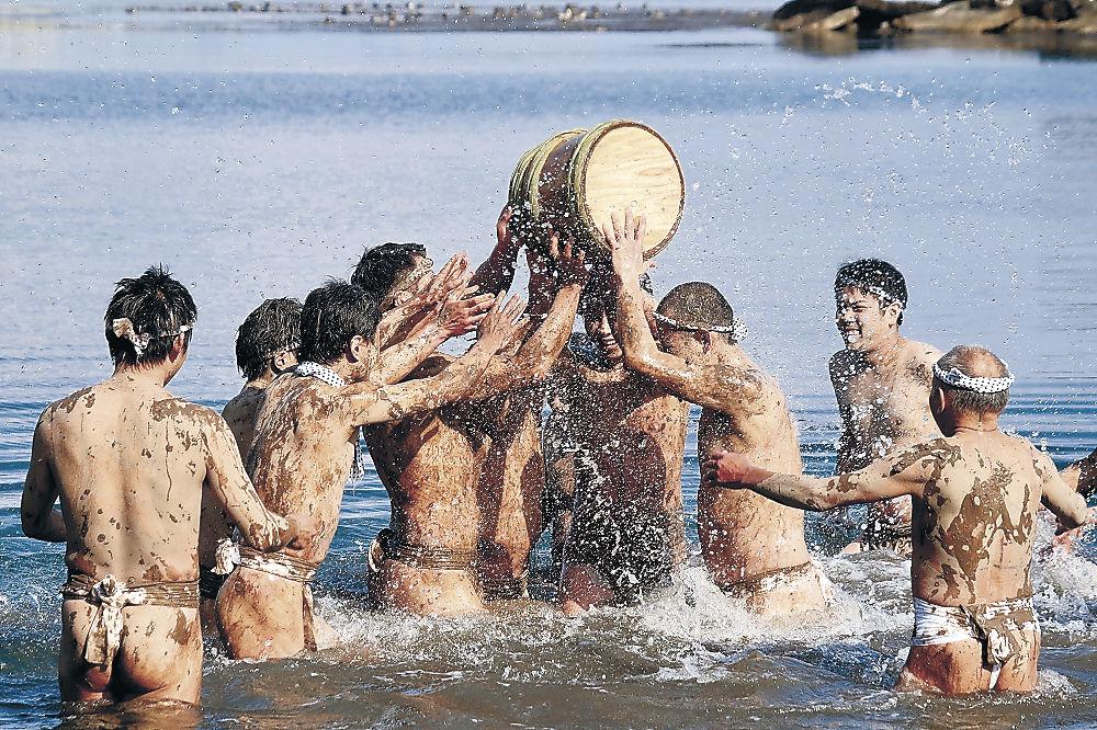水しぶきを上げながら樽を奪い合う男衆=能登町藤波