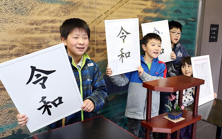 「令和」と書かれた額を手に記念撮影する子どもたち=高岡市万葉歴史館