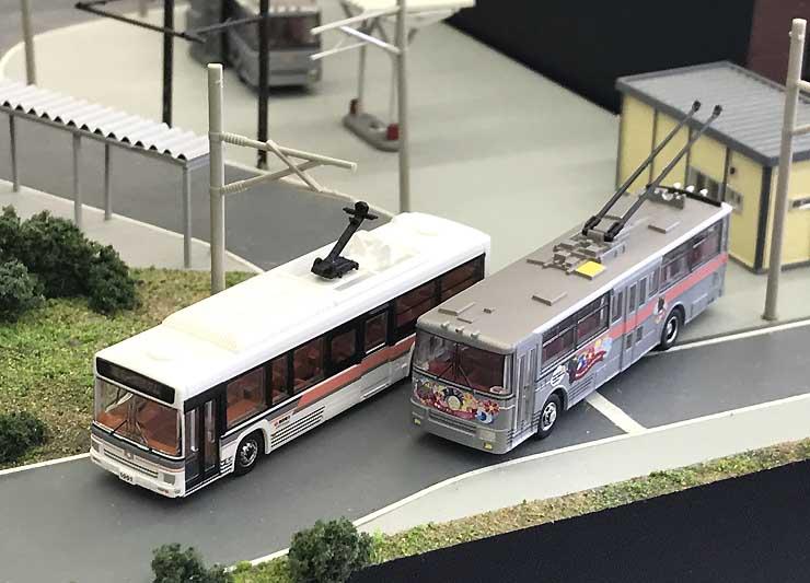 関電トンネル電気バスの模型(左)と、トロリーバスラストイヤーラッピング版の模型