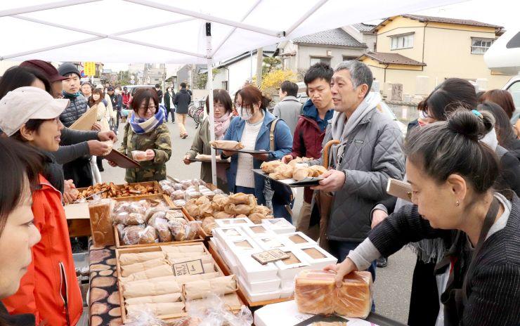 カップルや家族連れでにぎわった沼垂テラス商店街の朝市=7日、新潟市中央区