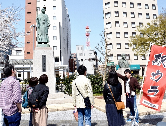 岡田元首相と松尾大佐の像を紹介する山元さん(右)=4月6日、福井県福井市日之出1丁目