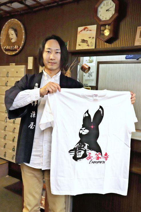 伊藤善行さんと、伊藤さんの発案で製作されたウサギ観音Tシャツ=佐渡市真野新町