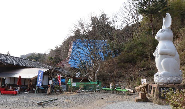 ウサギ観音(右)が人気を博す一方、庫裏(中央)の屋根が台風で吹き飛んだままの長谷寺=佐渡市長谷
