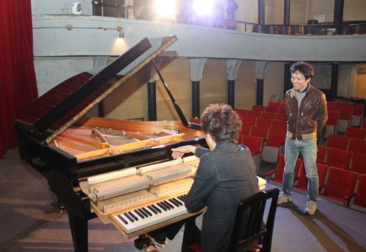 高田世界館に期間限定で導入されたグランドピアノ。調律技能士が音色や状態を確認した=9日、上越市本町6