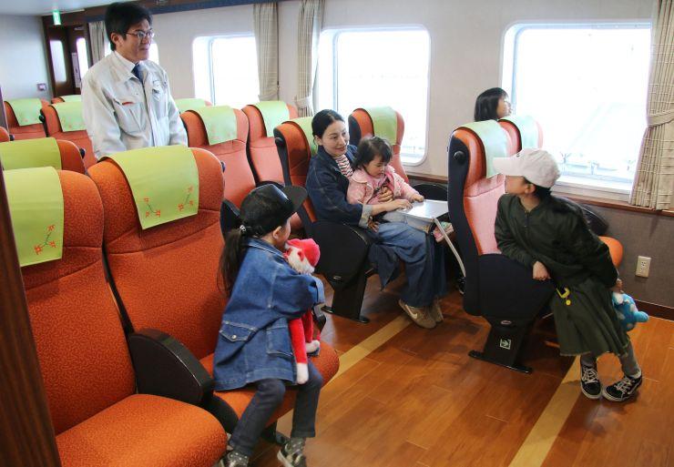 粟島汽船の新造船「フェリーニューあわしま」の船内を見学する人たち=13日、村上市