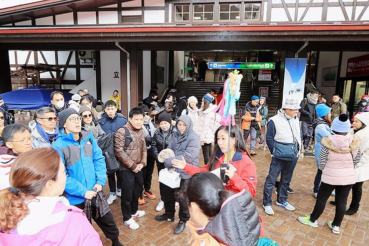 ガイドから高原バスの終日運休を聞き、がっかりした様子の観光客=立山駅