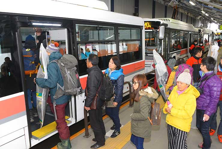 扇沢駅で気バスの第1便に乗り込む観光客=15日、大町市