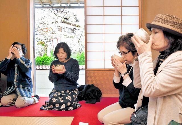 丸岡城を望む茶室で抹茶を堪能する観光客ら=4月14日、福井県坂井市の丸岡城天守前広場にある茶室「霞城菴」